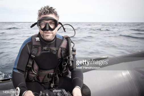 A scuba diver rides on an inflatable boat