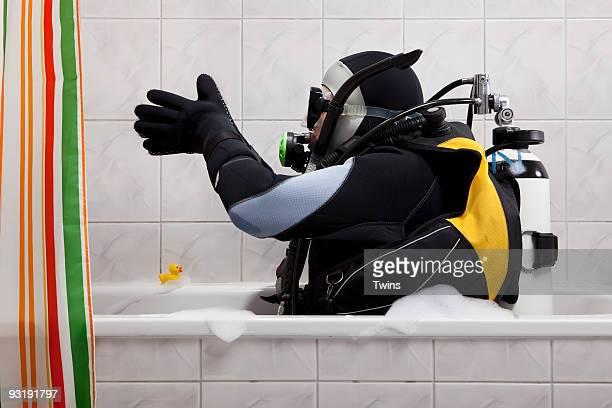 A scuba diver sitting in a bathtub preparing to dive in
