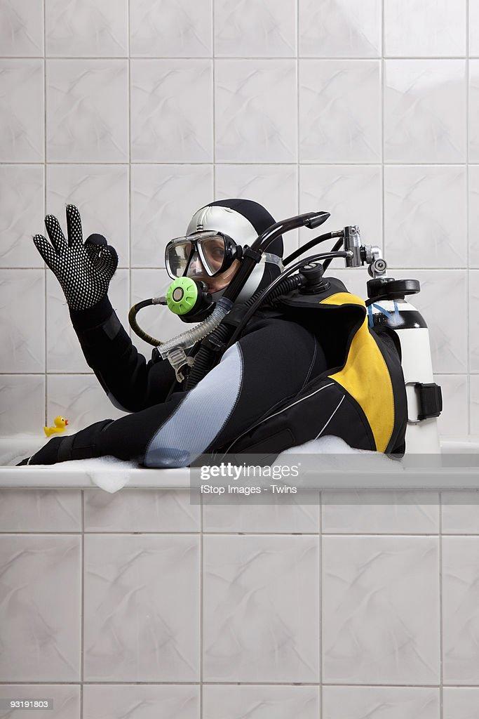 A scuba diver sitting in a bubble bath giving the OK sign