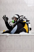 A scuba diver sitting in a bubble bath giving the OK sign
