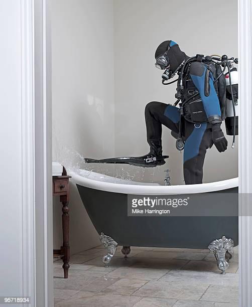 Scuba diver standing in a bath