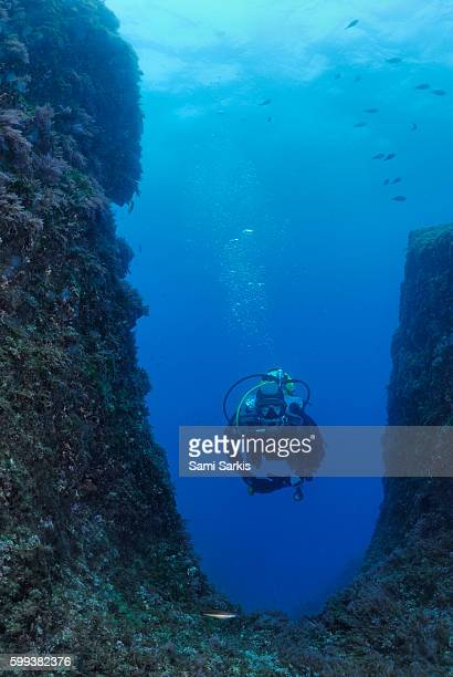 Scuba diver swimming by underwater rock formation, Mediterranean Sea, France, Europe