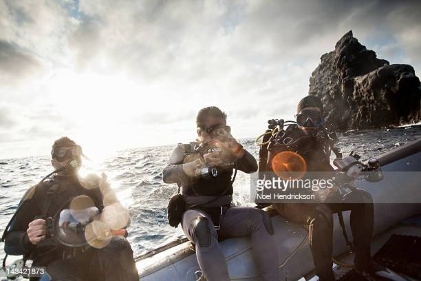 Scuba divers dive off of an inflatable boat