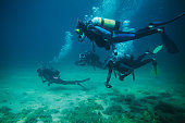 Group of divers underwater with scuba equipment and two of them with action cameras.