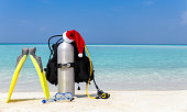 Scuba diving equipment with Santa Claus hat on tropical beach