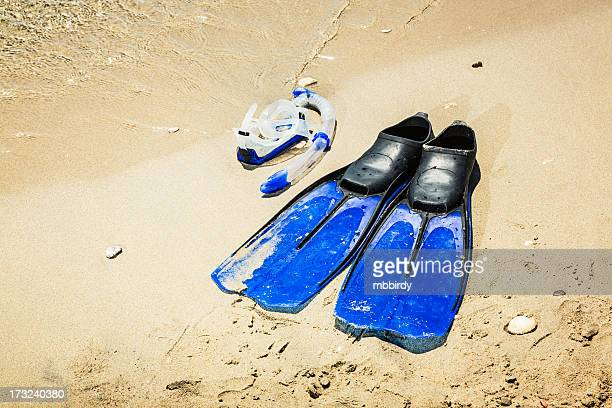Scuba diving mask and fins on sandy beach