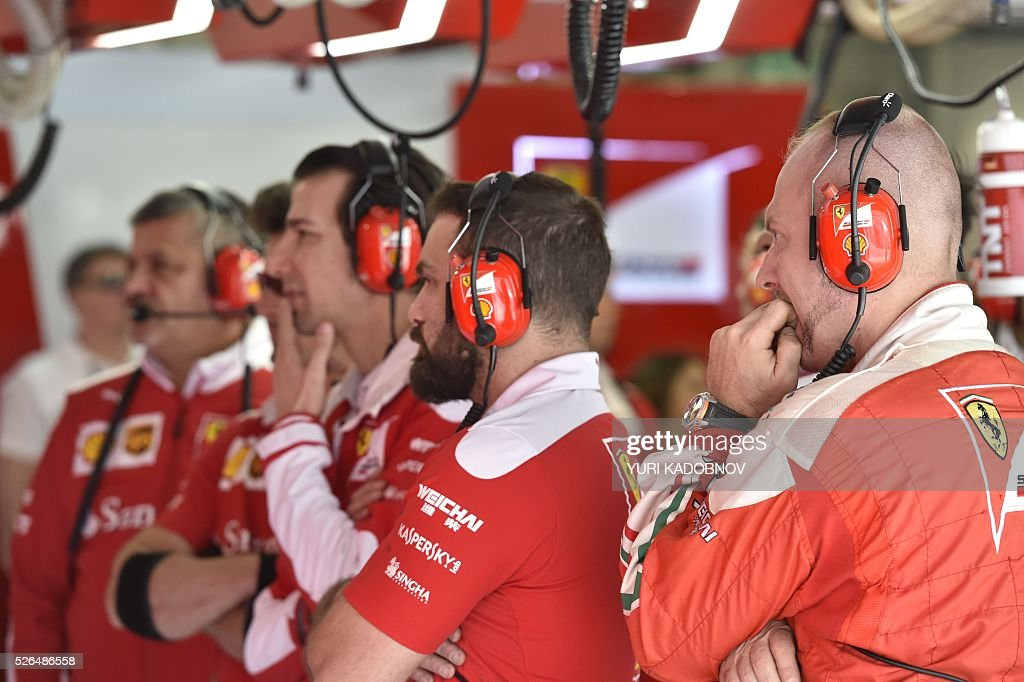 Scuderia Ferrari crew members look at screens in the pits during the third practice session of the Formula One Russian Grand Prix at the Sochi Autodrom circuit on April 30, 2016. / AFP / YURI