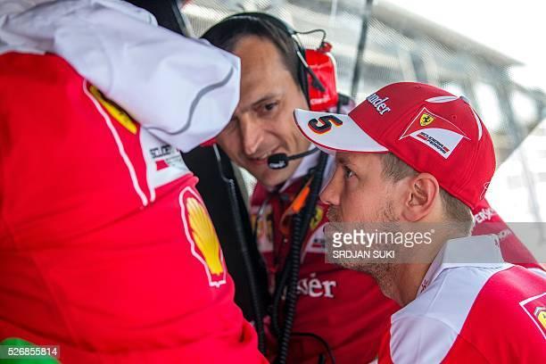 Scuderia Ferrari's German driver Sebastian Vettel looks at screens in the pits after crashing during the Formula One Russian Grand Prix at the Sochi...
