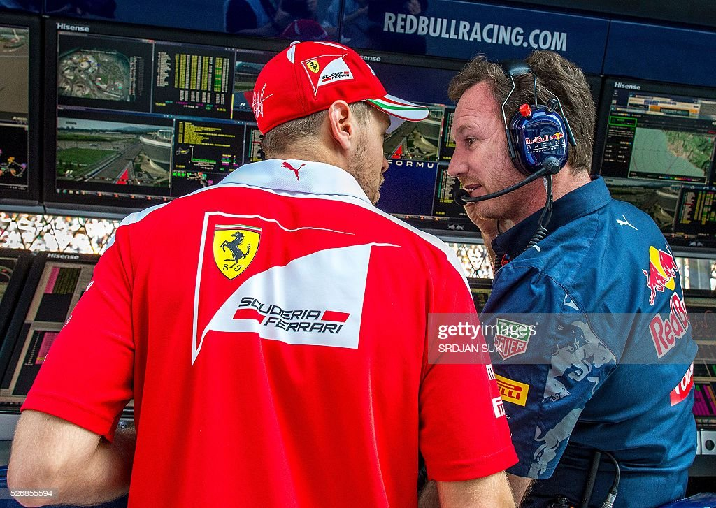 Scuderia Ferrari's German driver Sebastian Vettel (L) talks to Red Bull Racing Team Principal Christian Horner in the pits during the Formula One Russian Grand Prix at the Sochi Autodrom circuit on May 1, 2016. / AFP / POOL / Srdjan Suki