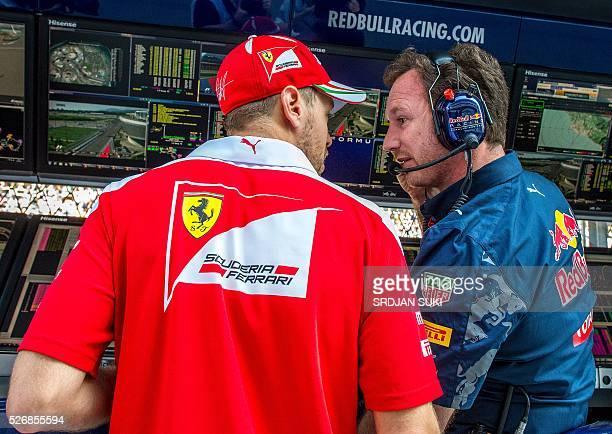 Scuderia Ferrari's German driver Sebastian Vettel talks to Red Bull Racing Team Principal Christian Horner in the pits during the Formula One Russian...