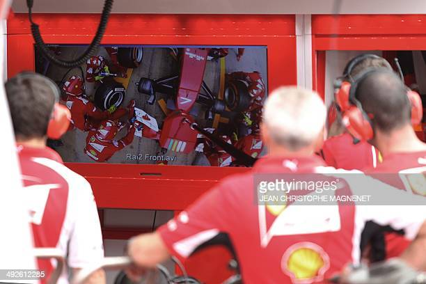 Scuderia Ferrari's mecanics look at a screen during training preparations in the pit at the Circuit de Monaco in Monte Carlo on May 21 ahead of the...