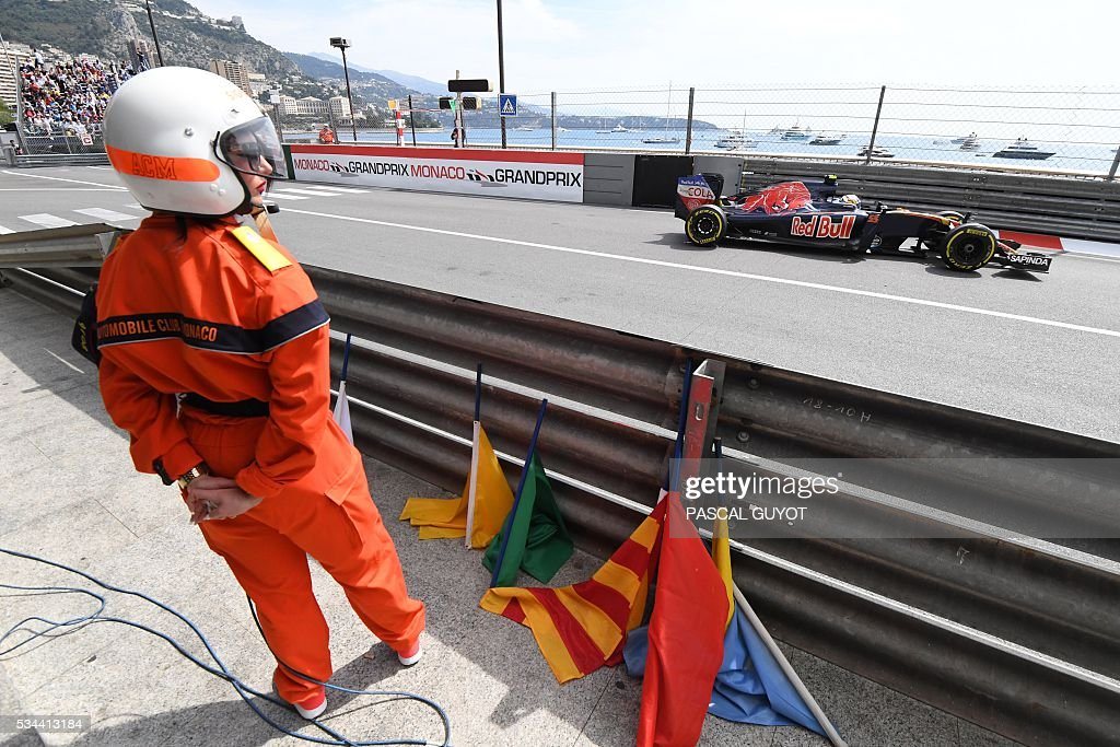 Scuderia Toro Rosso's Spanish driver Carlos Sainz Jr drives as a track marshall looks at him during the first practice session at the Monaco street circuit, on May 26, 2016 in Monaco, three days ahead of the Monaco Formula 1 Grand Prix. / AFP / PASCAL