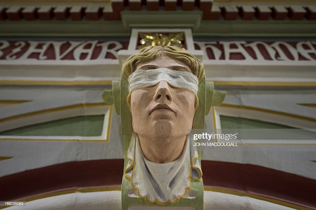A sculpted head with a blindfold (symbolising the ojectivity of justice) can be seen above a door frame leading into a courtroom in the newly restored regional court house (Landgericht) in Halle, eastern Germany, on May 6, 2013. The neo-Baroque building, which combines Gothic, Renaissance and Art Nouveau styles, was completed in 1905. The building's 20 courtrooms, 110 offices were painstakingly renovated over a two-year period, and will officially reopen for business in May 2013.