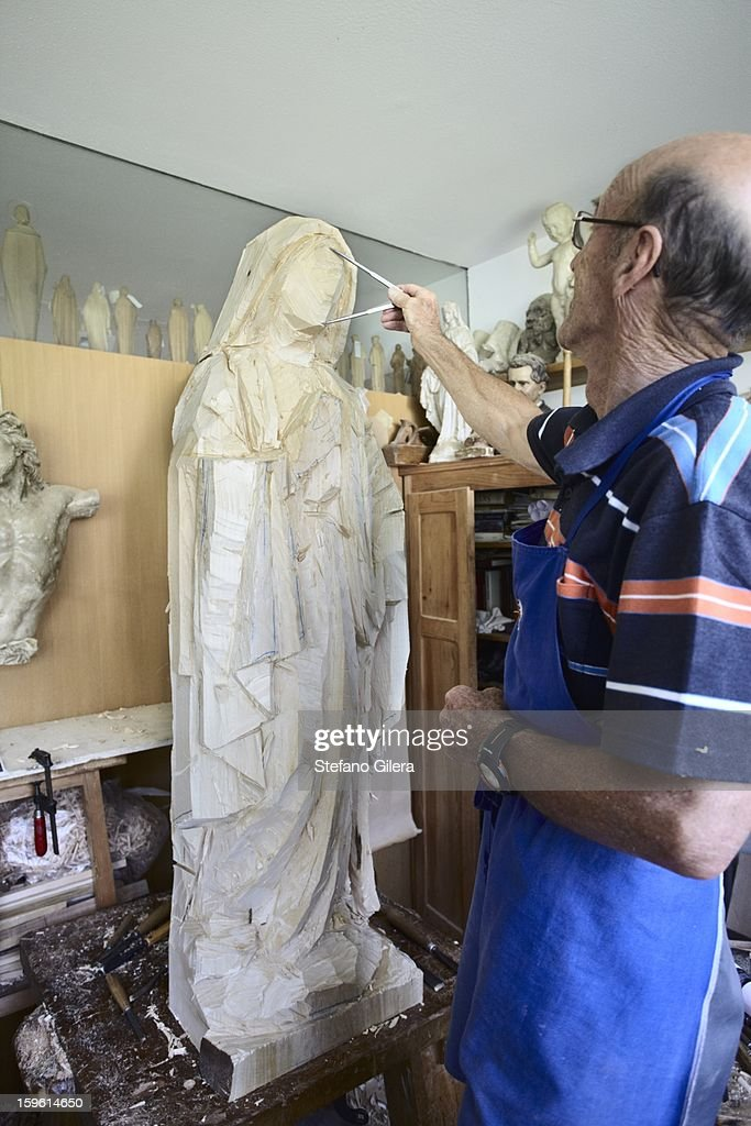 Sculptor admiring wood figure : Stock Photo