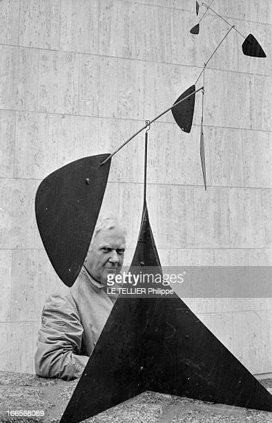 Sculptor Alexander Calder Makes A Mobile For The Palace Of Unesco A Paris devant le palais de l'UNESCO Alexandre CALDER en imperméable posant...