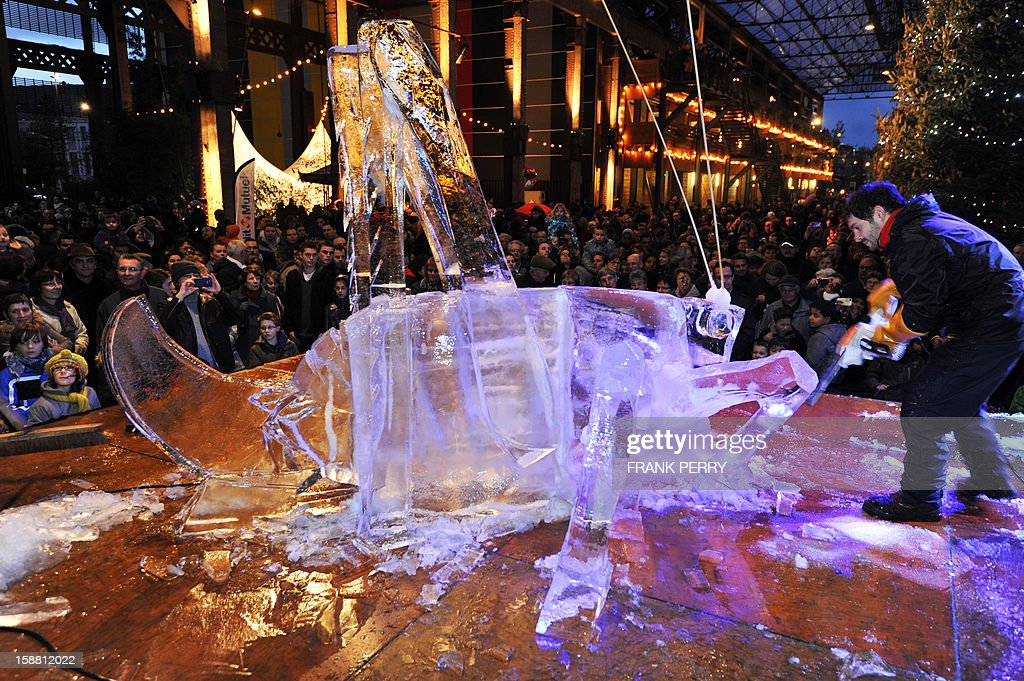 A sculptor carves a block of ice into a cricket, in front of the crowd at the Machines de l'Ile, an artistic venue in Nantes, western France, on December 30, 2012.
