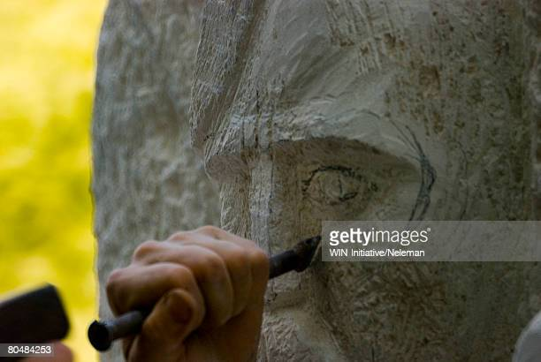 Sculptor carving eye of statue, close-up