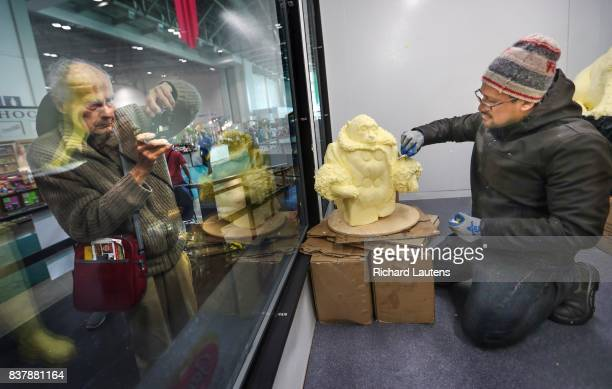 TORONTO ON AUGUST 22 Sculptor David Salazar puts some finishing touches on a butter Ikea Monkey as spectators look on Butter sculptors at this year's...