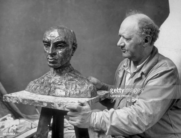 Sculptor Jacob Epstein with the finished bust of Pandit Nehru prime minister of India Nehru posed for Epstein during his recent visit to London for...