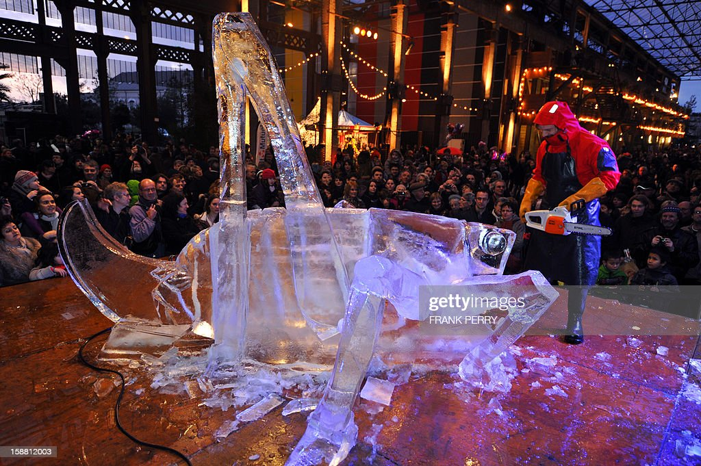 A sculptor looks at his work as he carves a block of ice into a cricket, in front of the crowd at the Machines de l'Ile, an artistic venue in Nantes, western France, on December 30, 2012.