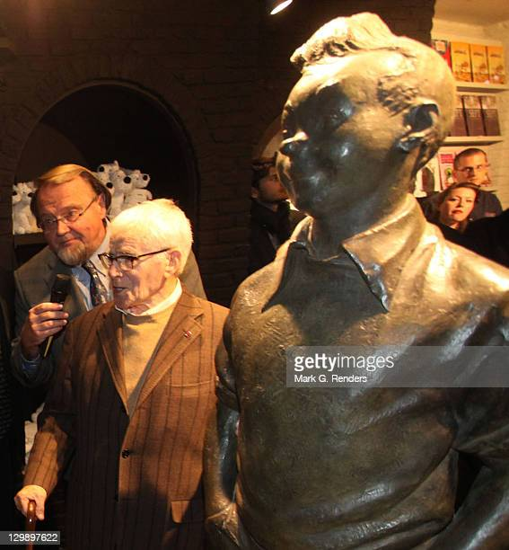 Sculptor Nat Neujean poses with his sculpture of the comic hero Tintin during its inauguration at The Comics Village on October 21 2011 in Brussels...