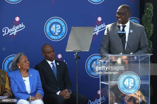 Sculptor of the Jackie Robinson statue Branly Cadet speaks onstage as Rachel Robinson left and Kevin Frazier look on during the Los Angeles Dodgers...