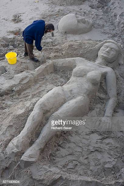 A sculptor shapes the female form of an oversized woman sunbather made from sand on the Thames foreshore on London's South Bank Working with great...