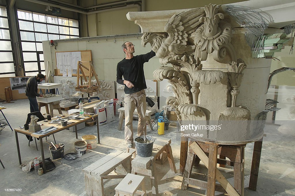 Sculptor Steffen Werner (R) creates a Corinthian capital with clay as his colleague Oleg Bessonov works ona rosette at the Schlossbauhuette studio where a team of sculptors is creating decorative elements for the facade of the Berliner Schloss city palace on November 11, 2011 in Berlin, Germany. The Berliner Schloss was the residence of the Prussian Kaiser and was among the major architectural landmarks of Berlin until it was heavily damaged by Allied bombing in 1945. The communist authorities of East Berlin demolished the building in the 1950s, and today's Berlin government is pursuing an ambitious project to rebuild the palace according to a design by Italian architect Franco Stella, which will recreate the facade of the building but with a modern interior at a cost of approximately EUR 590 million. The Humboldt Forum, the foundation leading the project, has given the Schlossbauhuette sculptors the formidable task of recreating the hundreds of architectural elements that decorated the facade, and though some original pieces were saved, more often the sculptors have only old black and white photos as reference.