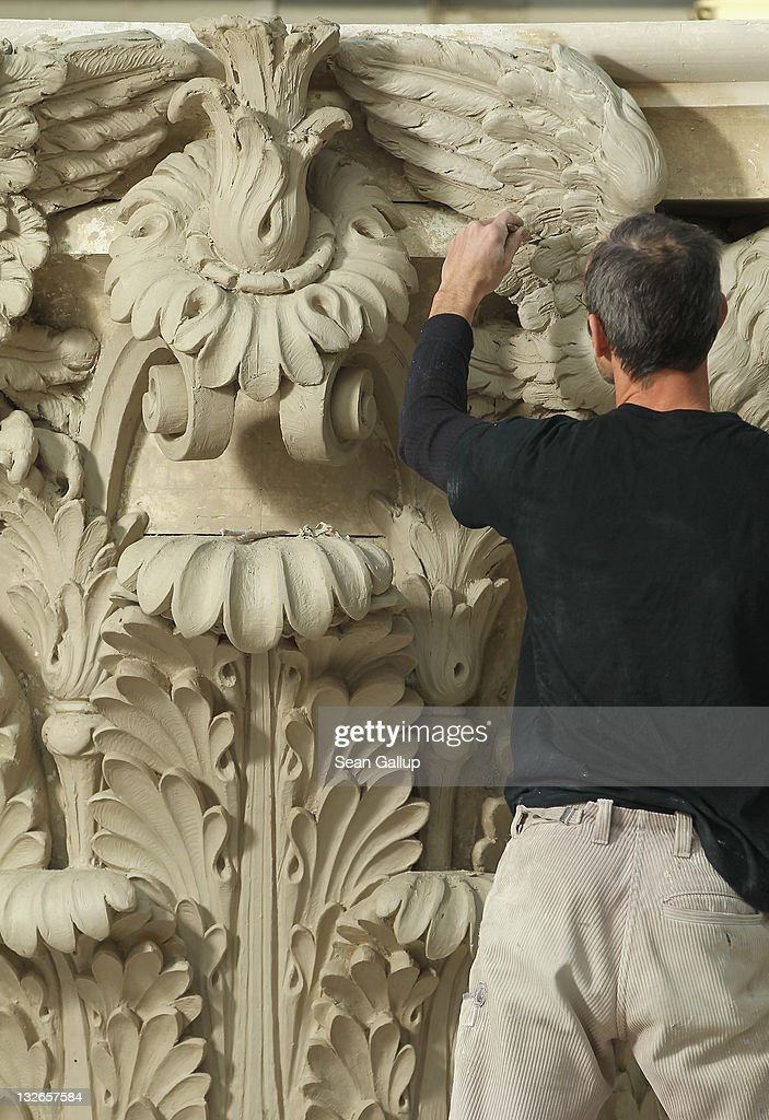 Sculptor Steffen Werner creates a Corinthian capital with clay at the Schlossbauhuette studio where a team of sculptors is creating decorative elements for the facade of the Berliner Schloss city palace on November 11, 2011 in Berlin, Germany. The Berliner Schloss was the residence of the Prussian Kaiser and was among the major architectural landmarks of Berlin until it was heavily damaged by Allied bombing in 1945. The communist authorities of East Berlin demolished the building in the 1950s, and today's Berlin government is pursuing an ambitious project to rebuild the palace according to a design by Italian architect Franco Stella, which will recreate the facade of the building but with a modern interior at a cost of approximately EUR 590 million. The Humboldt Forum, the foundation leading the project, has given the Schlossbauhuette sculptors the formidable task of recreating the hundreds of architectural elements that decorated the facade, and though some original pieces were saved, more often the sculptors have only old black and white photos as reference.