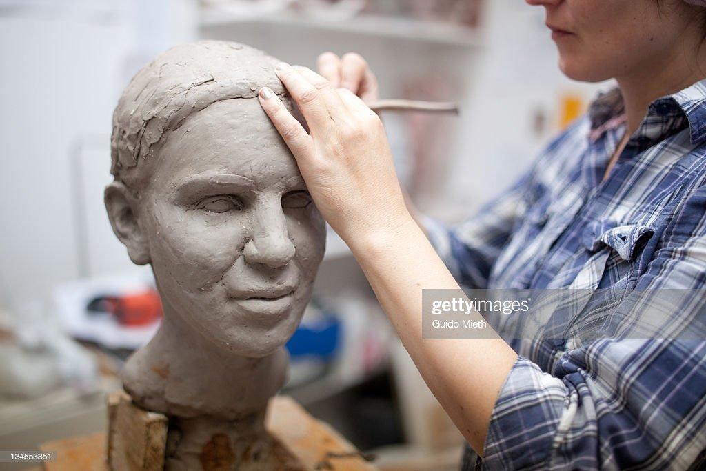 Sculptor working on female sculpture.
