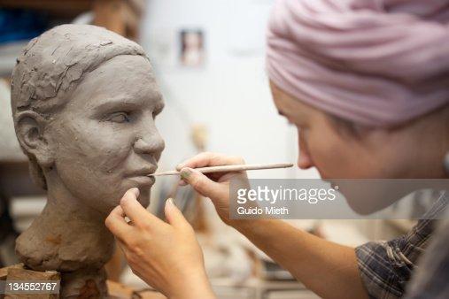 Sculptor working on head sculpture.