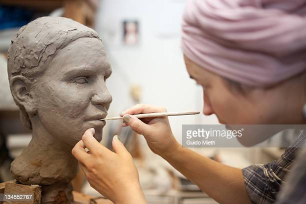 Sculptor working on head sculpture.