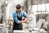 Handsome sculptor brushing stone head sculpture on the table in the atmospheric studio