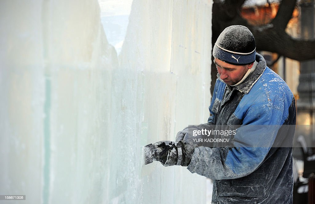 A sculptor works on a wall of the ice fortress in a park in central Moscow on December 23, 2012. A cold wave of weather hit this week the Russian capital. The temperatures in Moscow reached today to - 20C. AFP PHOTO / YURI KADOBNOV