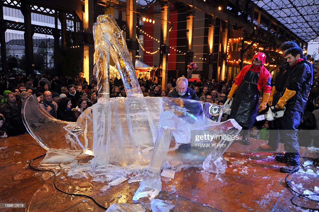 Sculptors carve a block of ice into a cricket, in front of the crowd at the Machines de l'Ile, an artistic venue in Nantes, western France, on December 30, 2012.