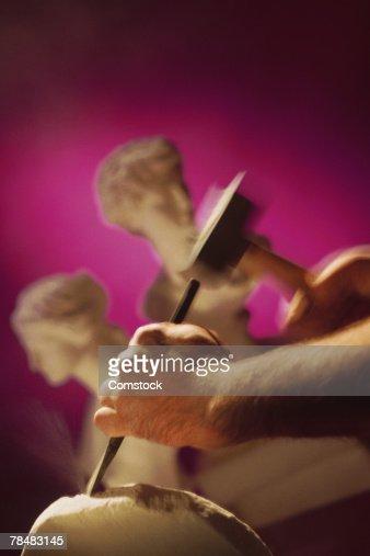 Sculptor's hands chiseling statue