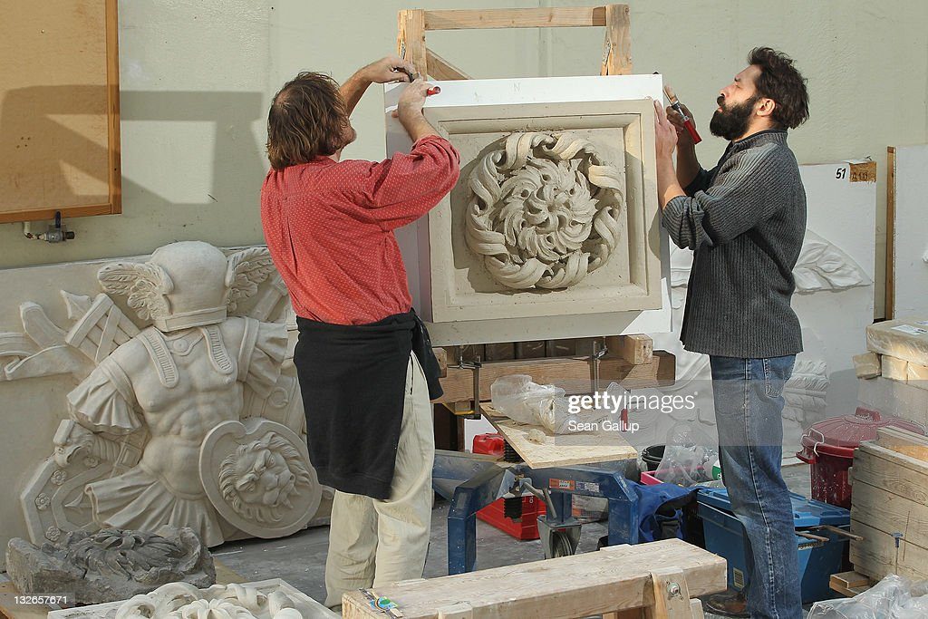 Sculptors Jens Cacha (L) and Oleg Bessonov set a partially-completed rosette on an easel at the Schlossbauhuette studio where a team of sculptors is creating decorative elements for the facade of the Berliner Schloss city palace on November 11, 2011 in Berlin, Germany. The Berliner Schloss was the residence of the Prussian Kaiser and was among the major architectural landmarks of Berlin until it was heavily damaged by Allied bombing in 1945. The communist authorities of East Berlin demolished the building in the 1950s, and today's Berlin government is pursuing an ambitious project to rebuild the palace according to a design by Italian architect Franco Stella, which will recreate the facade of the building but with a modern interior at a cost of approximately EUR 590 million. The Humboldt Forum, the foundation leading the project, has given the Schlossbauhuette sculptors the formidable task of recreating the hundreds of architectural elements that decorated the facade, and though some original pieces were saved, more often the sculptors have only old black and white photos as reference.