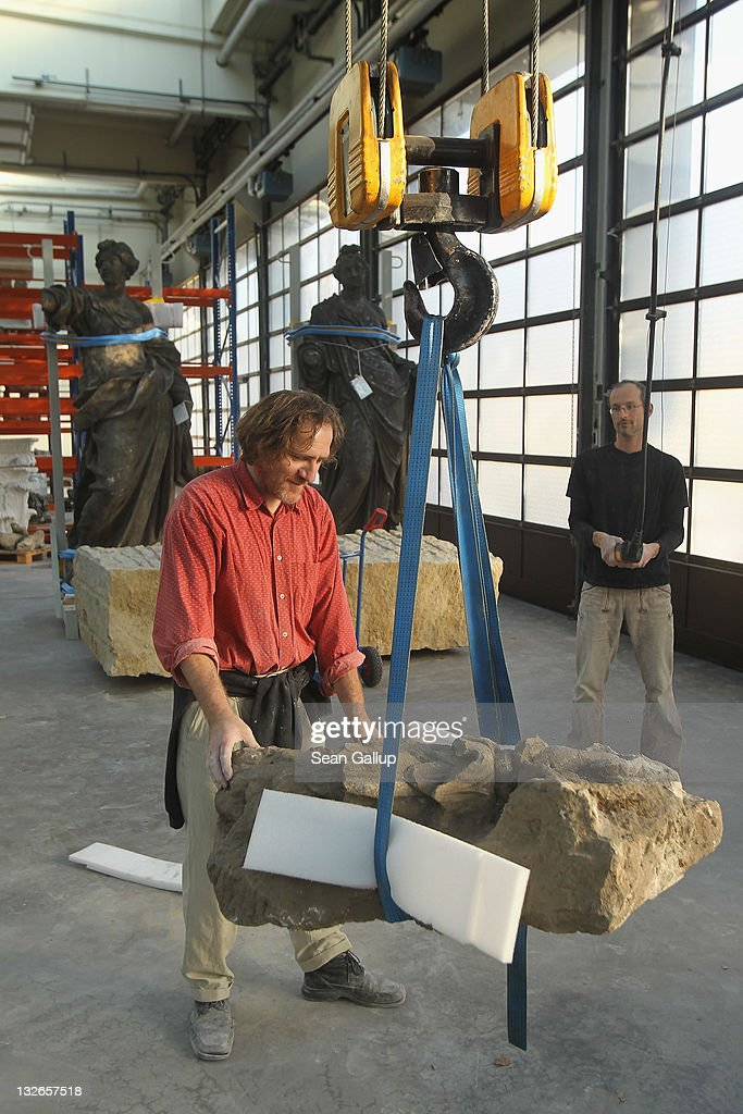 Sculptors Jens Cacha (L) and Steffen Werner use a winch to move a damaged original stone garland from the Berliner Schloss at the Schlossbauhuette studio where a team of sculptors is creating decorative elements for the facade of the Berliner Schloss city palace on November 11, 2011 in Berlin, Germany. The Berliner Schloss was the residence of the Prussian Kaiser and was among the major architectural landmarks of Berlin until it was heavily damaged by Allied bombing in 1945. The communist authorities of East Berlin demolished the building in the 1950s, and today's Berlin government is pursuing an ambitious project to rebuild the palace according to a design by Italian architect Franco Stella, which will recreate the facade of the building but with a modern interior at a cost of approximately EUR 590 million. The Humboldt Forum, the foundation leading the project, has given the Schlossbauhuette sculptors the formidable task of recreating the hundreds of architectural elements that decorated the facade, and though some original pieces were saved, more often the sculptors have only old black and white photos as reference.