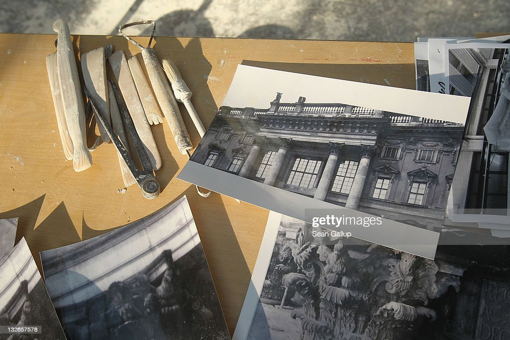 A sculptor's tools lie among old photographs depicting architectural details of the original Berliner Schloss on a worktable at the Schlossbauhuette studio, where a team of sculptors is creating decorative elements for the facade of the Berliner Schloss city palace on November 11, 2011 in Berlin, Germany. The Berliner Schloss was the residence of the Prussian Kaiser and was among the major architectural landmarks of Berlin until it was heavily damaged by Allied bombing in 1945. The communist authorities of East Berlin demolished the building in the 1950s, and today's Berlin government is pursuing an ambitious project to rebuild the palace according to a design by Italian architect Franco Stella, which will recreate the facade of the building but with a modern interior at a cost of approximately EUR 590 million. The Humboldt Forum, the foundation leading the project, has given the Schlossbauhuette sculptors the formidable task of recreating the hundreds of architectural elements that decorated the facade, and though some original pieces were saved, more often the sculptors have only old black and white photos as reference.