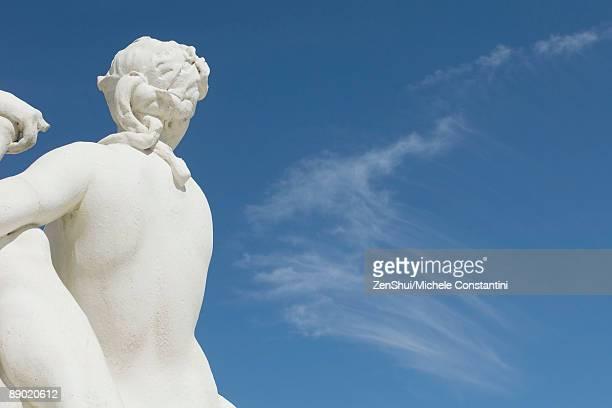 Sculpture looking toward blue sky, rear view