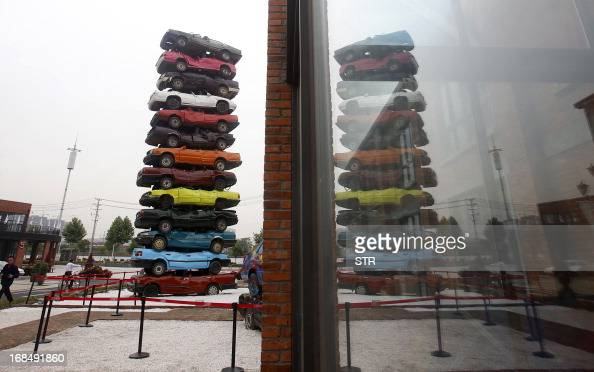A sculpture made of retired cars is reflected on the window of a building in 'Jiangcheng No1' Creative Culture Park in Wuhan central China's Hubei...