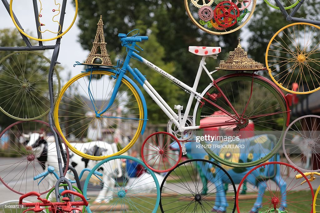 A sculpture made with a bike and wheels is displayed near in Le Mont-Saint-Michel, on June 29, 2016, three days before the start of the 103rd edition of the Tour de France cycling race. The 2016 Tour de France will start on July 2 in the streets of Le Mont-Saint-Michel and ends on July 24, 2016 down the Champs-Elysees in Paris. / AFP / KENZO