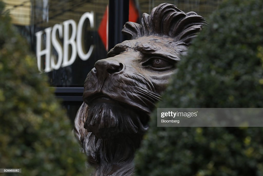 A sculpture of a lion, seen through hedges, sits outside the main entrance to the HSBC Holdings Plc headquarters in the Canary Wharf business, financial and shopping district in London, U.K., on Saturday, Feb. 13, 2016. HSBC's board will meet on Sunday to decide whether to shift its headquarters from London, according to two people with knowledge of the decision. Photographer: Luke MacGregor/Bloomberg via Getty Images