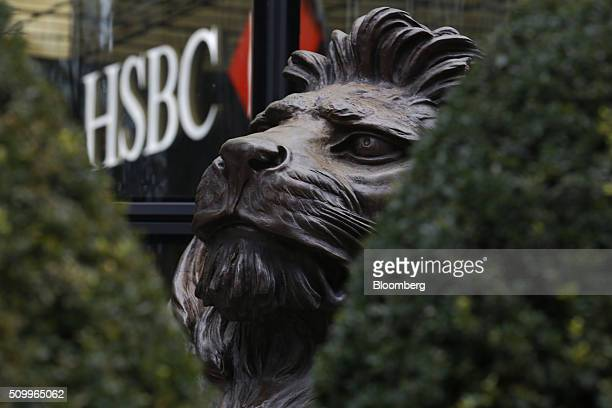 A sculpture of a lion seen through hedges sits outside the main entrance to the HSBC Holdings Plc headquarters in the Canary Wharf business financial...