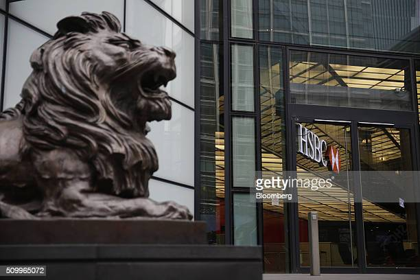 A sculpture of a lion sits outside the main entrance to the HSBC Holdings Plc headquarters in the Canary Wharf business financial and shopping...