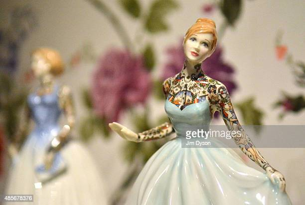 A sculpture of a tattooed porcelain figure by Jessica Harrison is displayed as Banksy's Dismaland Bemusement Park opens to the public on August 28...