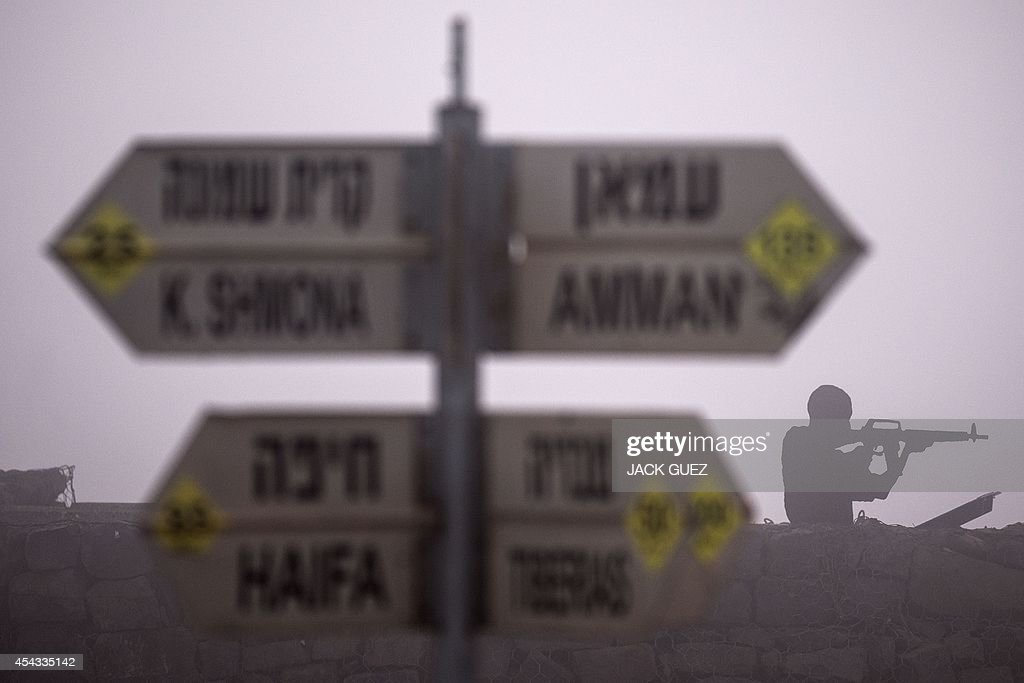 A sculpture of an Israeli soldier standing guard is seen next to a sign for tourists showing the different distances to Jerusalem, Baghdad, Damascus and other locations, at an army post in Mount Bental in the annexed Golan Heights, on August 29, 2014. Syrian rebels, including Al-Qaeda's affiliate Al-Nusra Front, seized control of the Syrian crossing with the Israeli-occupied Golan Heights, the Britain-based Syrian Observatory for Human Rights said.