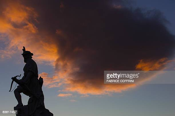 A sculpture of legendary Swiss hero William Tell holding his crossbow is seen in silhouette at sunset on November 25 2008 in Lausanne According to...