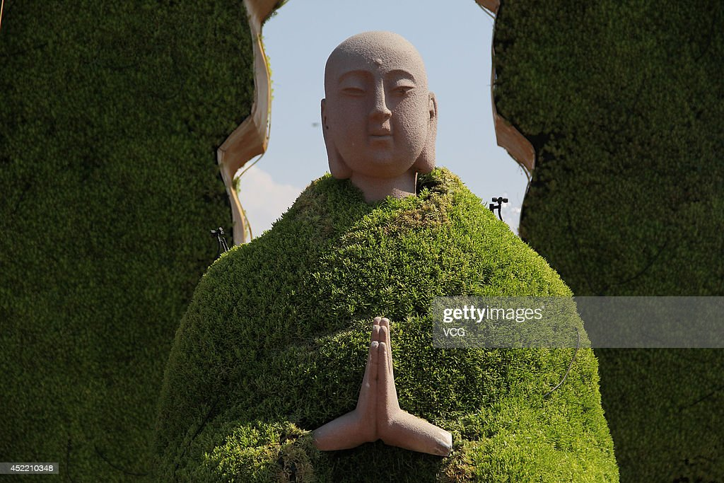XI'AN CHINA JULY 15 A sculpture of Monk Tang wearing a 'green coat' made up of green plants was seen on at Dayanta July 15 2014 in Xi'an Shaanxi...