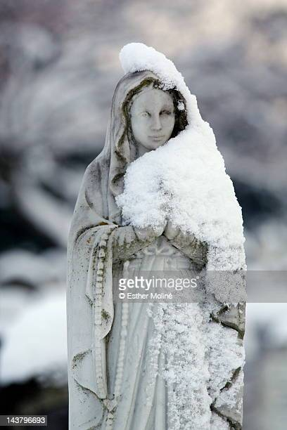 Sculpture of Virgin Mary with snow